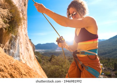 Woman stands on a large rock and belays the climber, climbing in Turkey, partner belaying, belay device and rope close-up, climber's hands