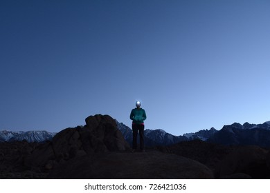 A woman stands on a rock at dusk. She has her hands in her pockets and is looking at the camera with a headlamp on. There are mountains and a clear, blue sky behind her.