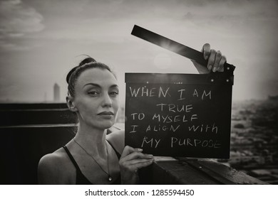 "The woman stands on the roof with a poster ""When I am true to myself, I align with my purpose"" International Womens Day  concept."