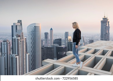 Woman stands on roof of skyscraper in Dubai, BayGate and Executive Towers at evening