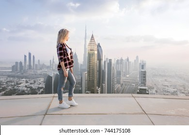 Woman stands on roof of skyscraper in Dubai at hot day, United Arab Emirates