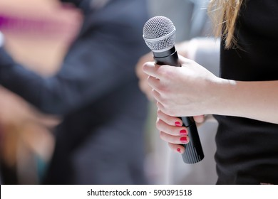 Woman stands on stage with microphone