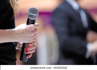 Woman stands on stage with microphone during speech