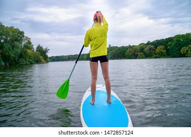 a woman stands on a SUP board on a large river on a cloudy day. Stand on the oars - great outdoor recreation