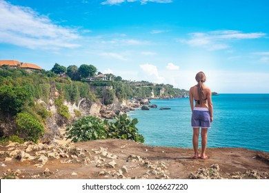 Woman stands on the top of mountain peak with sea view and enjoy the beautiful outdoor landscape, travel concept, Bali island, Indonesia. Freedom and happiness, beautiful young girl over sea shoreline