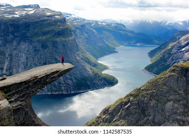 A woman stands on Trolltunga (Troll's Tongue), the cliff above the lake Ringedalsvatnet, a popular tourist destination in Hordaland county, Norway.