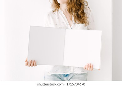 Woman stands with an open empty book. White book mockup. Opened square empty book. Album with a clean pages in hands. Clean book mock up. Mock-up is ready to design. Young woman with an album template