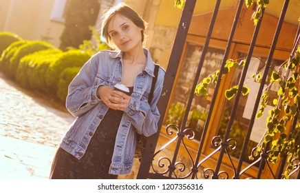 A woman stands in the rays of the setting sun with a cup of coffee. City portrait