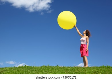 Woman stands in summer on grass and starts  large inflatable ball in blue sky