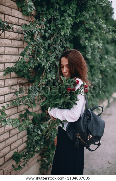 a woman stands in a white shirt and black pants. girl with a bouquet of flowers. girl in the garden amongst the plants. beautiful elegant brunette.