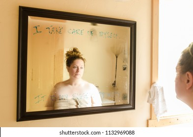 A woman stares at herself in a mirror that has a positive affirmation written but she is sad and disappointed with herself and life due to her weight issues