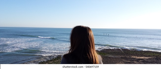 Woman staring at the sea on the beach