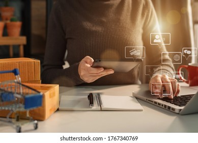 Woman start up small business owner writing address on cardboard box at workplace.small business entrepreneur SME or freelance asian woman working with box at home.