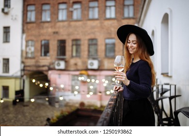 Woman stay on balcony and drink some wine. Pretty smiling woman with glass of wine. Holiday vibes and mood