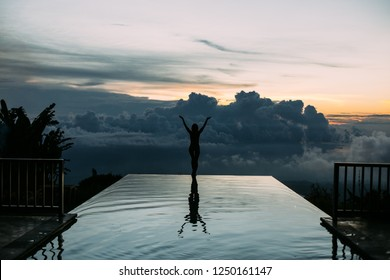 Woman stay on poolside, see on the sunset and feel free. Amazing sunset and great pool