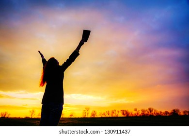 Woman staying with raised hands at the sunset time