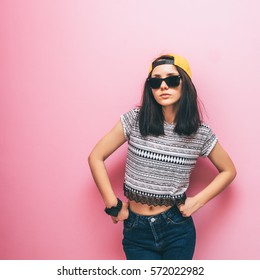 Woman stays in fashion pose in printed tee shirt and jeans.