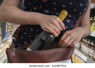 Woman is stealing bottle of wine and hiding it in handbag in supermarket.