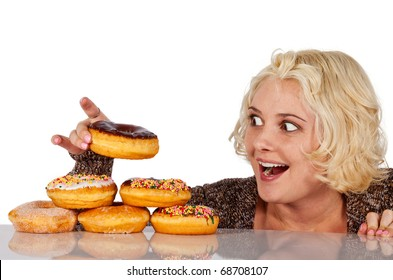 Woman steals a donut off a pile of donuts