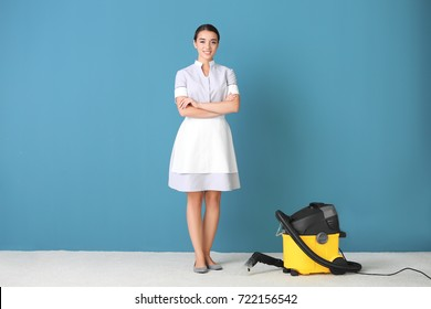 Woman with steam vapor cleaner near color wall