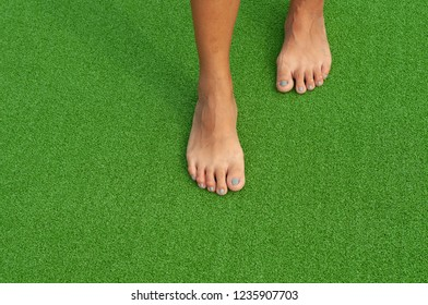 Woman step on green artificial grass without shoes