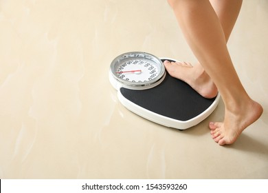 Woman stepping on floor scales indoors, space for text. Overweight problem