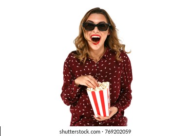 Woman in stereo glasses holding popcorn and posing in surprise on white background.