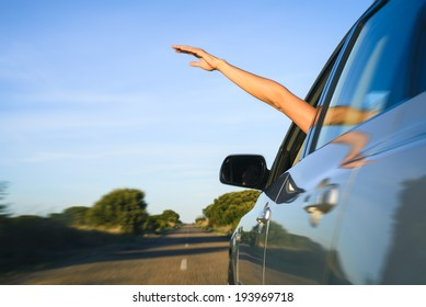 Woman sticking arm out of the car window on roadtrip. Female driver hand feeling the air and freedom.
