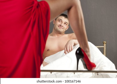 woman in stiletto seducing man in bed