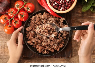 Woman stirring cooked minced meat in kitchen