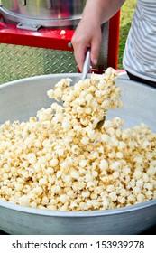 A woman stirs salt into a freshly popped batch of kettle corn.