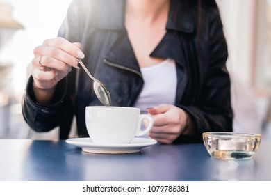 The woman stirs a spoonful of coffee and tea. The woman will sweeten her coffee with sugar. Misuse of sugar, use of sweeteners.