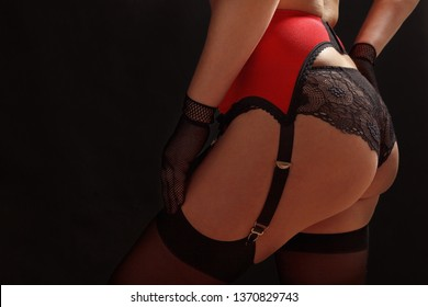 Woman in stockings, erotic stocking belt and panties on a black background close up