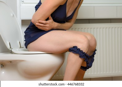 Woman with a stomach ache sitting on a toilet clutching her midriff with her arms with her blue panties around her knees, close up body view