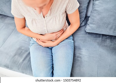 Woman with  stomach issues / problems while sitting on the couch.
