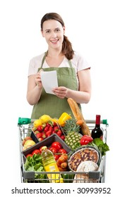 A woman in a store assistant role with a list on a white background and a cart full of fresh goods.