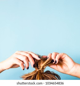 The woman straightens the disheveled bun on her head with her hands with a black manicure. Dark hair is tied with a transparent spiral elastic band. Modern fast hairstyle. Blue background. Copyspace