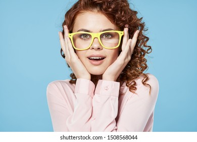Woman straightens glasses on her face curly hair pink shirt blue background