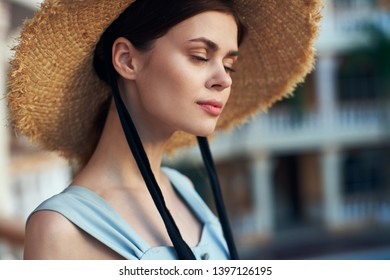 A woman in a straw hat with black ribbons and a blue sundress on a hotel balcony