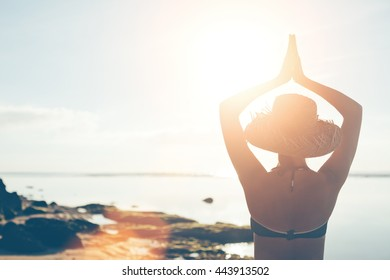 Woman in straw hat doing yoga early in the morning on the beach (intentional sun glare and lens flare effect)