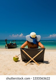 Woman with straw hat enjoying her holidays on a transat at the tropical beach in Thailand