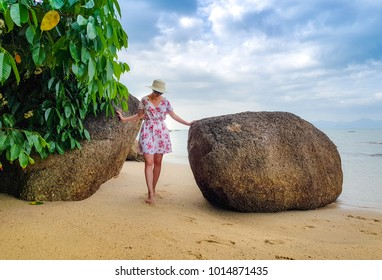 Woman with straw hat in flower dress on the beach
