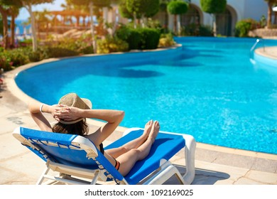 Woman in a straw hat relaxing on a daybed near a luxurious summer pool, concept time to travel.