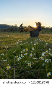 Woman with straw hat sitting in the field at sunset