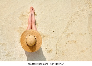 Woman in straw hat sitting on beach view from above. Summer vacation at Maldives.