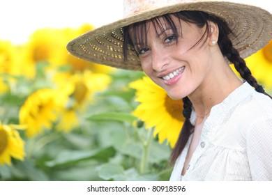Woman in a straw hat in a sunflower field