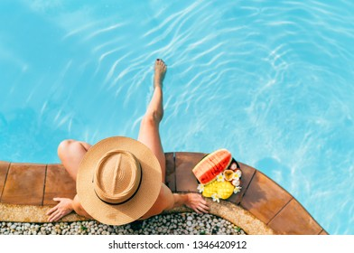 Woman in straw hat in swimming pool with plate of tropical fruits. Top view shot