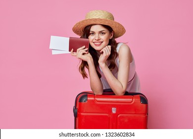 a woman in a straw hat and with tickets in her hands leaned on a red suitcase on a pink isolated background