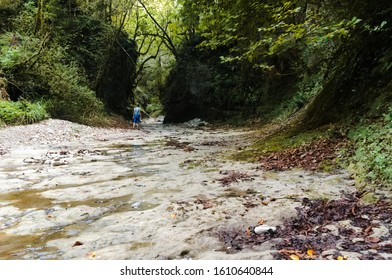Woman in the stream bed of a mountain river. The slopes of the mountain river bed are covered with wild plants. Now the river is almost dry due to snowless winters (climate change).