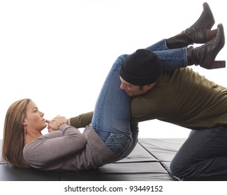 Woman in street clothes overpowering a mugger with an armbar on black mat